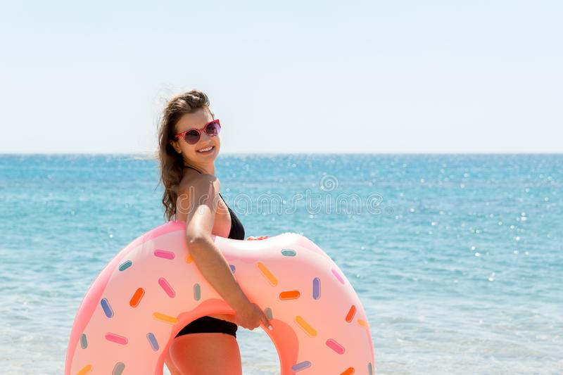 Beautiful sexy cute happy woman running on the beach with a pink rubber inflatable ring in the hand. Summer holidays and vacation. Concept royalty free stock photos