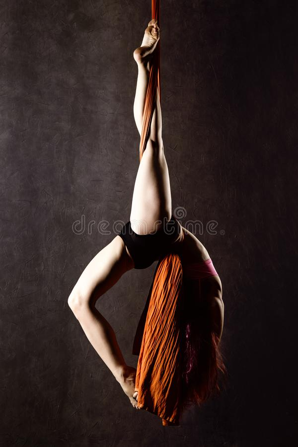 Beautiful dancer on aerial silk, graceful contortion, acrobat performs a trick on a ribbons royalty free stock photography