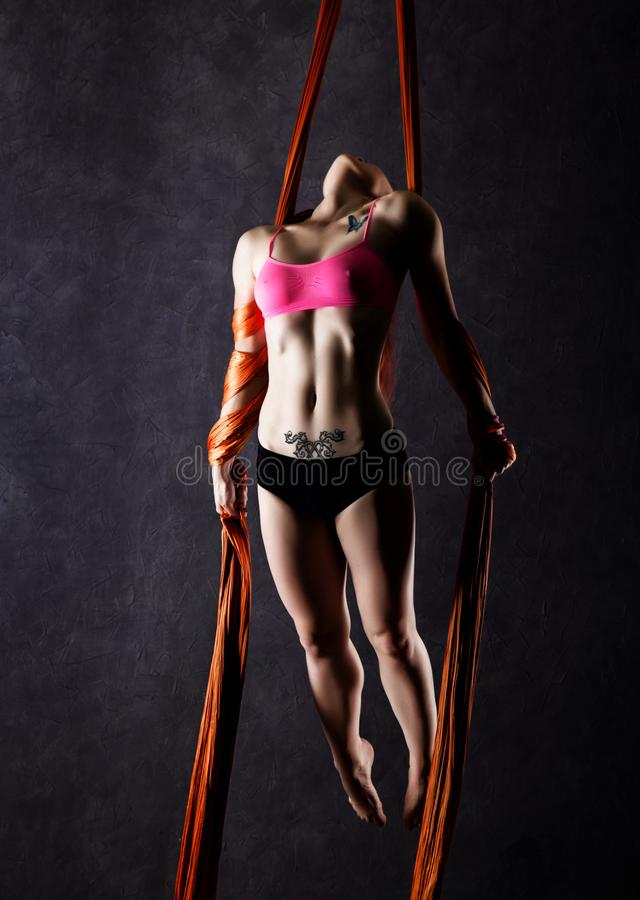 Beautiful dancer on aerial silk, graceful contortion, acrobat performs a trick on a ribbons.  stock image