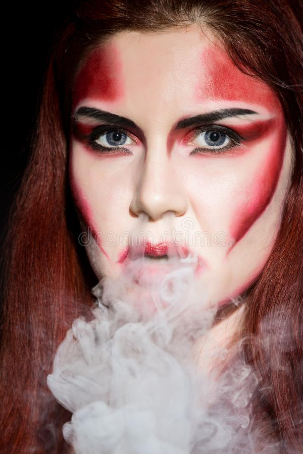 Beautiful devil girl with professional make-up. Fashion Art design. Attractive woman blows smoke from the nose royalty free stock photo