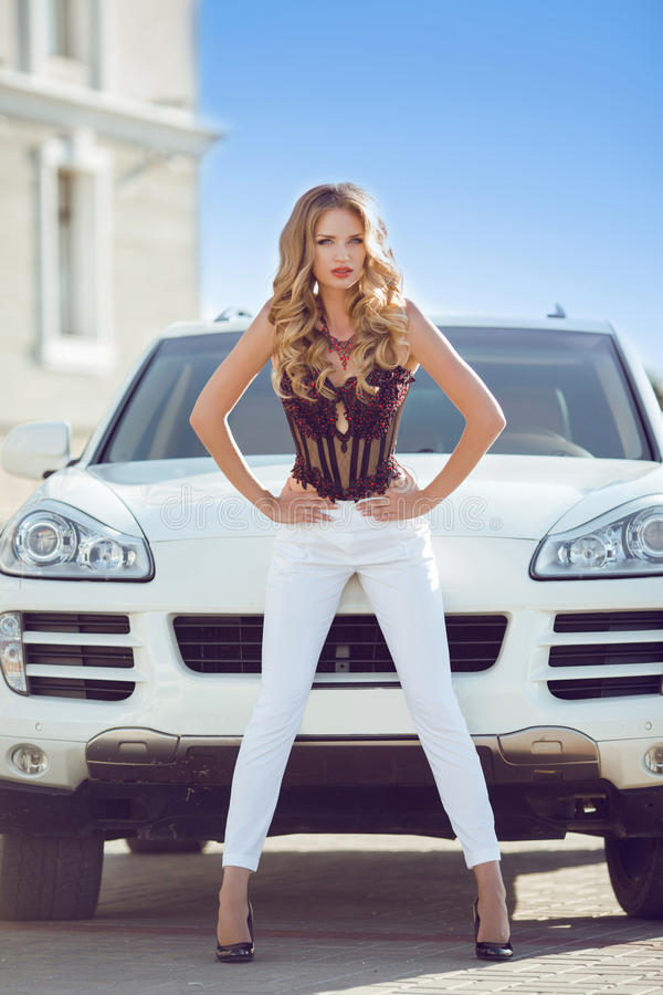 Beautiful Driver girl model with long legs posing in front. Of white car. Luxury style stock image