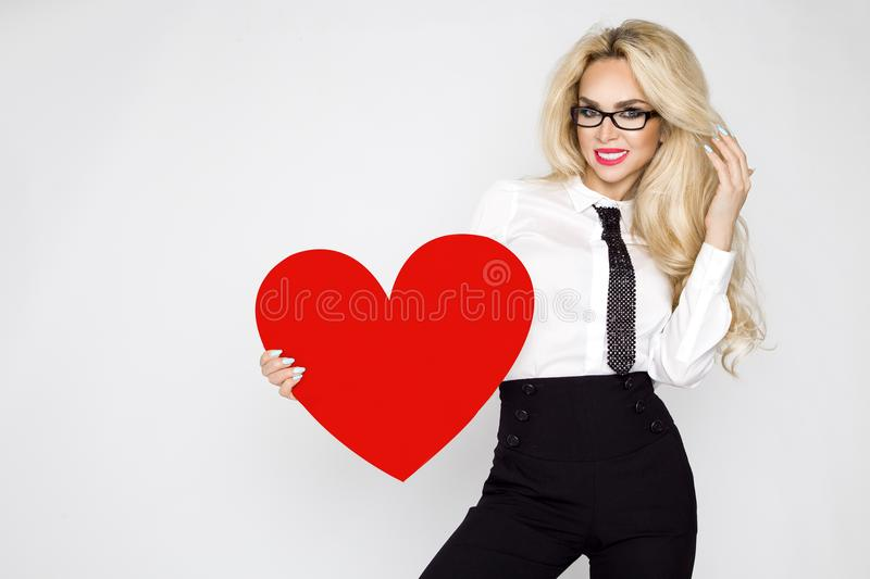 Beautiful, sexy, elegant blonde woman holding a red valentine heart stock images