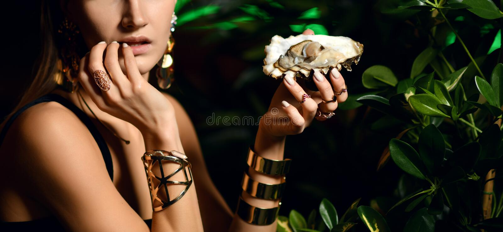 Beautiful fashion brunette woman in expensive interior restaurant eat oysters royalty free stock photography