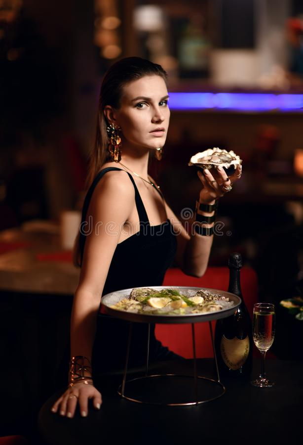 Beautiful fashion brunette woman in expensive interior restaurant eat oysters royalty free stock photos