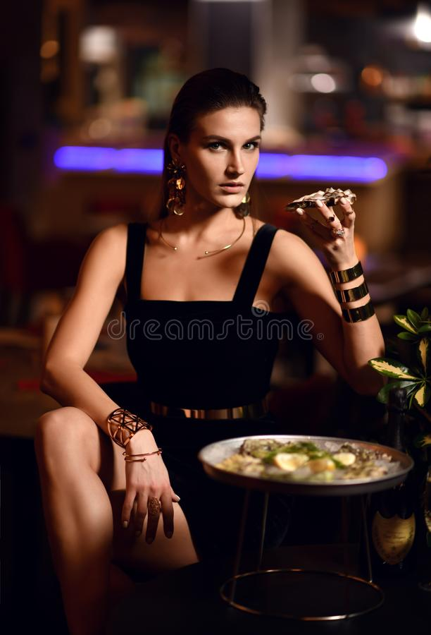 Beautiful fashion brunette woman in expensive interior restaurant eat oysters royalty free stock photo