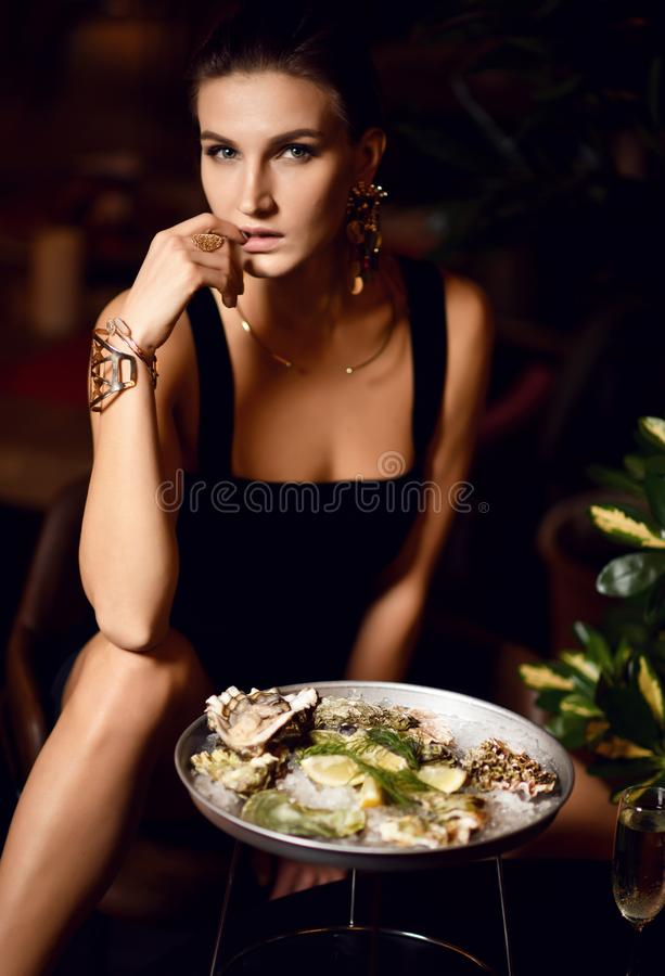 Beautiful fashion brunette woman in expensive interior restaurant eat oyster waiting. Beautiful fashion brunette woman in expensive interior restaurant eat stock images