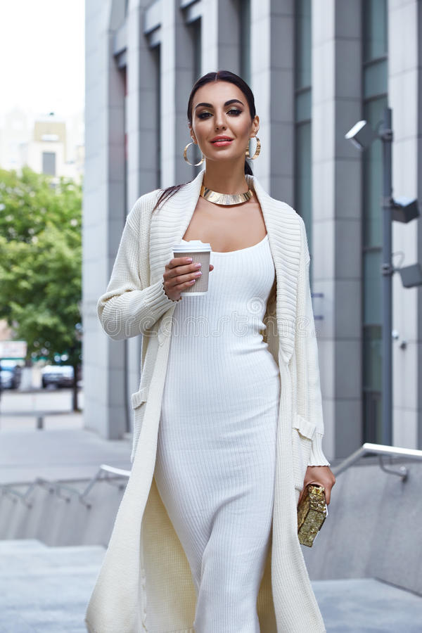 Beautiful fashion glamour woman walk city street. Modern building architecture dark hair natural makeup chic slinky dress knit wool long coat jacket accessory stock photography