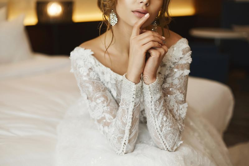 Beautiful, and fashionable brown-haired young woman, in a lace dress, posing in interior - bride`s morning stock photo