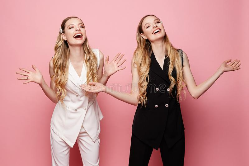 Beautiful, sexy and fashionable twins, two happy and smiling blonde young model girls in sleeveless jackets and pants stock images