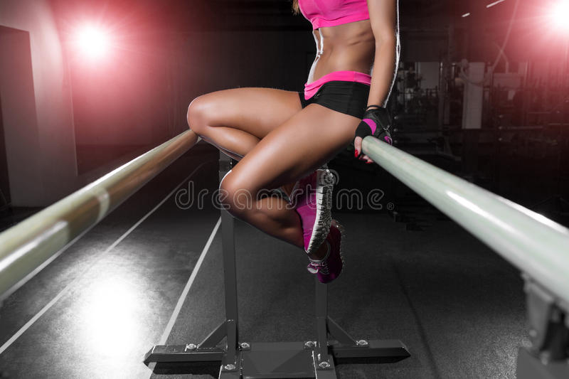 Beautiful female athlete posing on parallel bars in gym. Preparation for exercises fitness girl in gym stock image