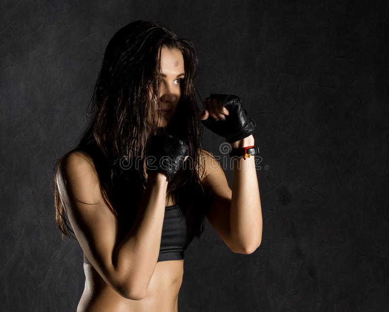 Beautiful female boxer or mma fighter wearing black gloves on a dark background.  royalty free stock photo