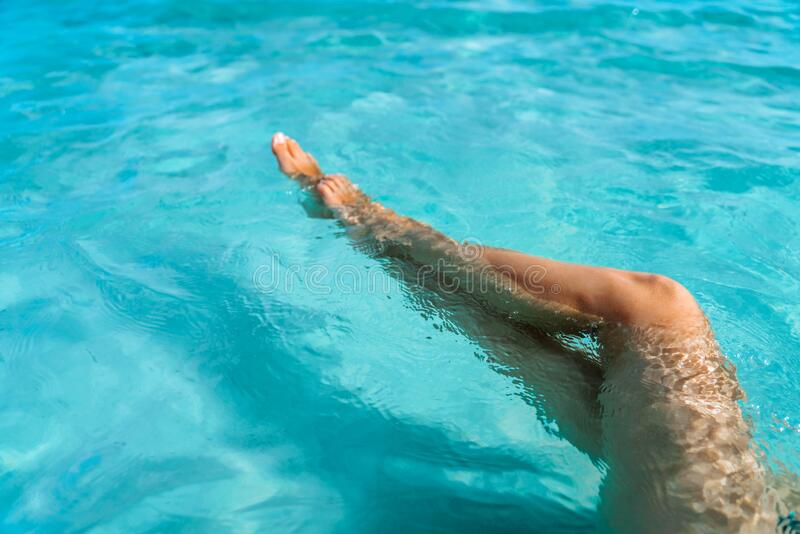 Beautiful sexy female legs in clear turquoise sea water. Beautiful young girl bathing. On a sandy beach royalty free stock photo