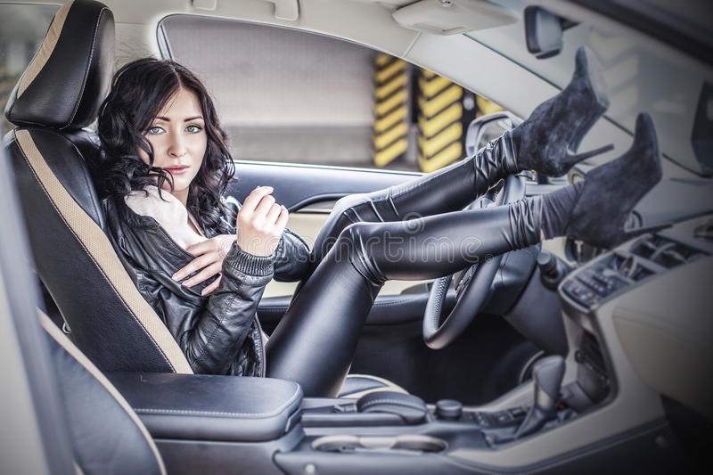 Beautiful female model with a white car in the Parking lot stock photo