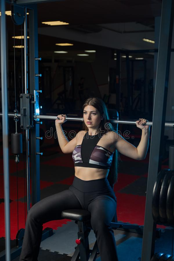 Beautiful fitness model shakes a barbell sitting from behind the head in the gym. stock image