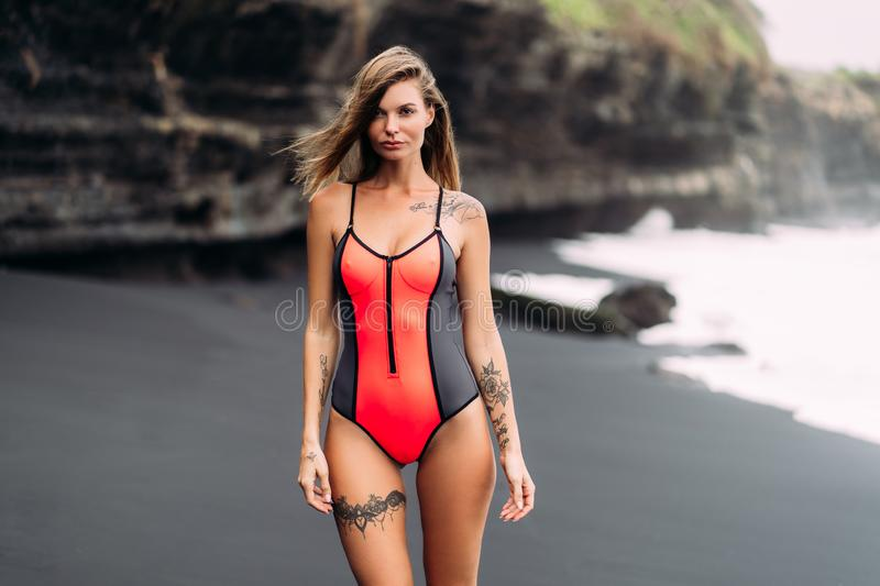 Beautiful sexy girl with big breasts in red swimsuit poses on black sand beach stock photography