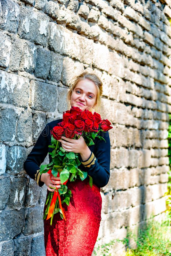 Beautiful and girl with a bouquet of red roses stands on the background of an old brick wall. stock images