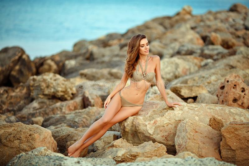 Beautiful girl with a chic figure in a swimsuit sits on stones against the sea royalty free stock photography
