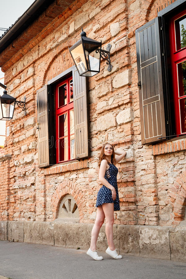 Beautiful girl with a hairdo and make-up in a dress is stan. Ding by a brick building with beautiful red windows in the city stock photo
