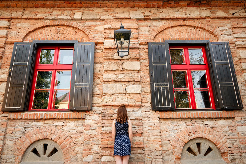 Beautiful girl with a hairdo and make-up in a dress is stan. Ding by a brick building with beautiful red windows in the city stock images