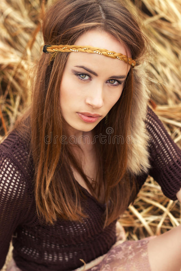 Beautiful girl hippies sitting in the dry grass royalty free stock photos