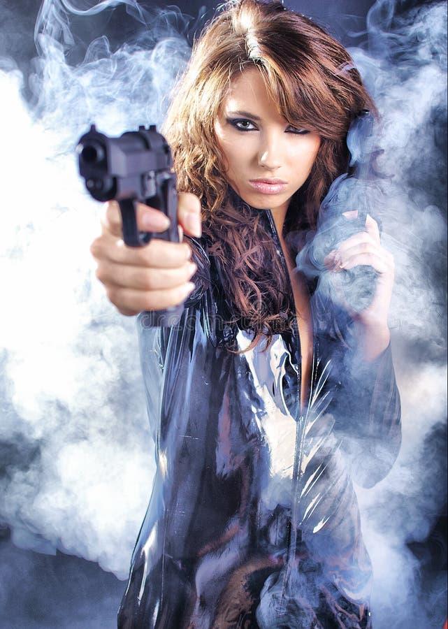 Beautiful girl holding gun royalty free stock images