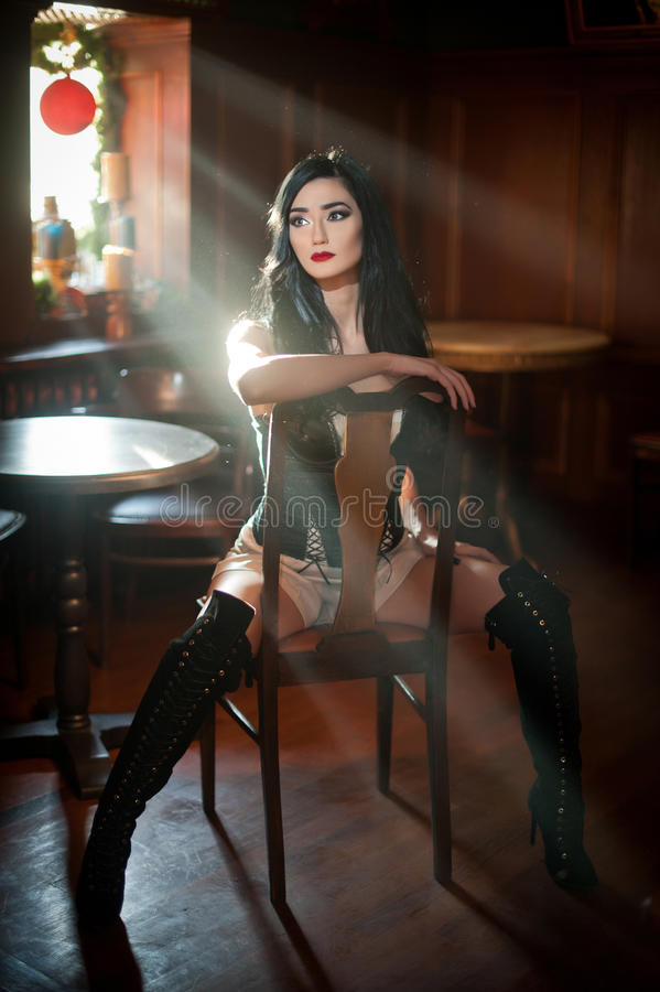 Beautiful girl with long leather boots sitting on chair in comfortable position. Brunette woman posing challenging. Sensual female with black corset and high royalty free stock photos