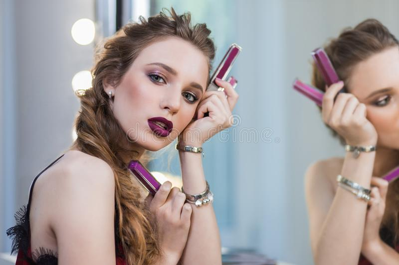 Beautiful girl with professional makeup at the mirror, advertises cosmetics, lipstick stock image