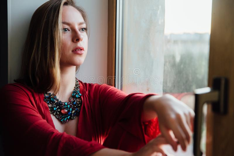 Beautiful girl in a red robe is sitting on the windowsill at home. stock images