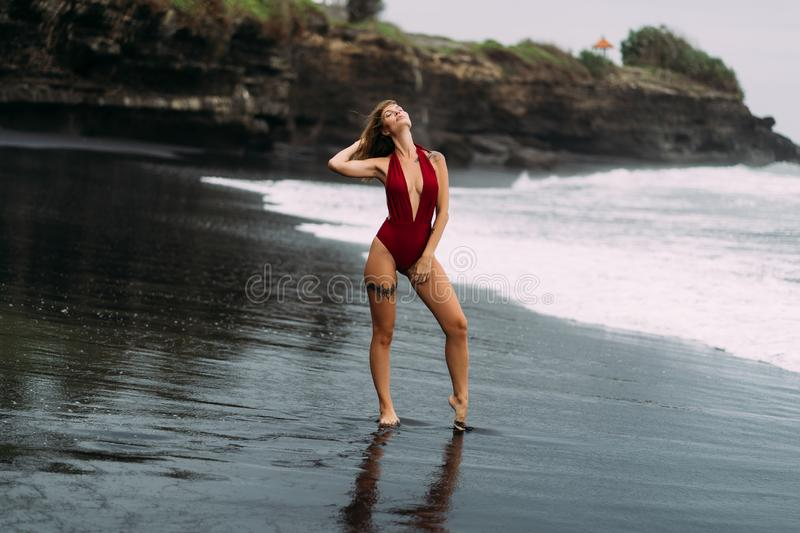 Beautiful sexy girl in red swimsuit poses on black sandy beach with rocks royalty free stock photos