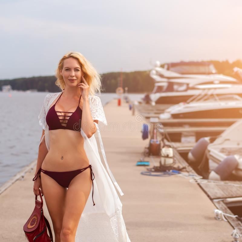 Beautiful sexy girl with a slim figure is standing on a wooden pier in a yacht club. Near motor yachts royalty free stock photos
