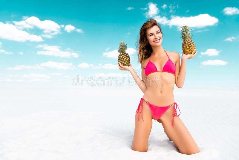 Beautiful sexy girl in swimsuit with pineapples on sandy beach with blue sky and clouds. Smiling beautiful sexy girl in swimsuit with pineapples on sandy beach stock photo