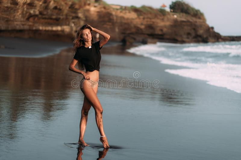 Beautiful sexy girl in T-shirt and swimsuit walks on black sandy beach at sunset royalty free stock photography