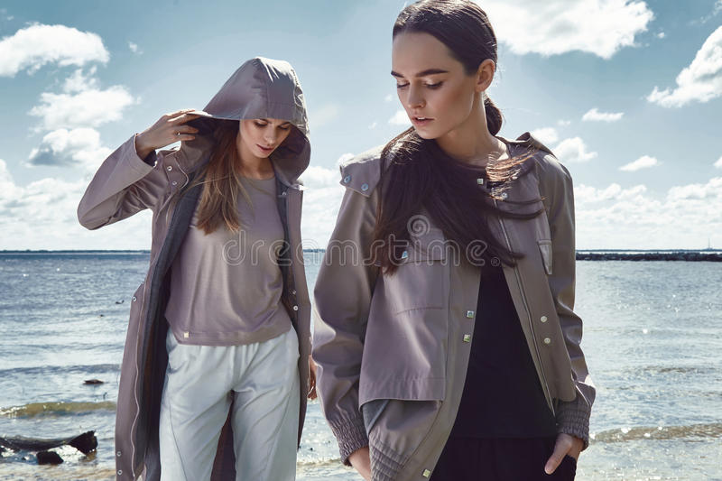 Beautiful girl walk in rock stone beach ocean sea summer. Autumn weather sun shine wear suit jacket long blond and brunette hair natural makeup catalog of royalty free stock photos
