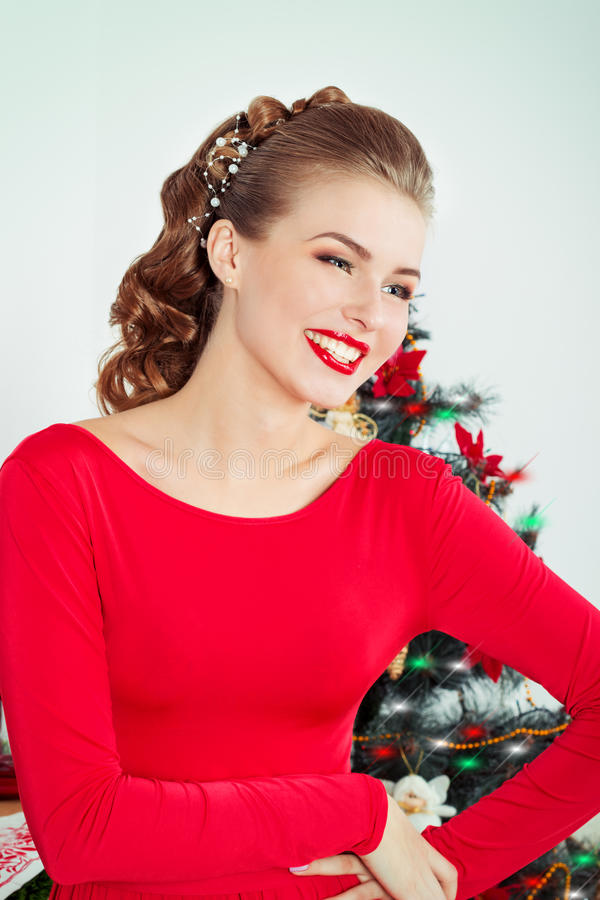 Beautiful happy smiling young woman in evening dress with bright makeup with red lipstick sitting near the Christmas tree stock photo