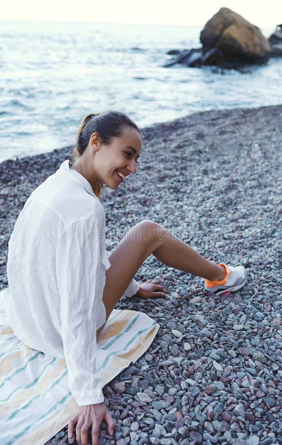 Beautiful happy woman having fun on beach at resort. Young smiling woman in a white shirt is sitting on a stony royalty free stock images