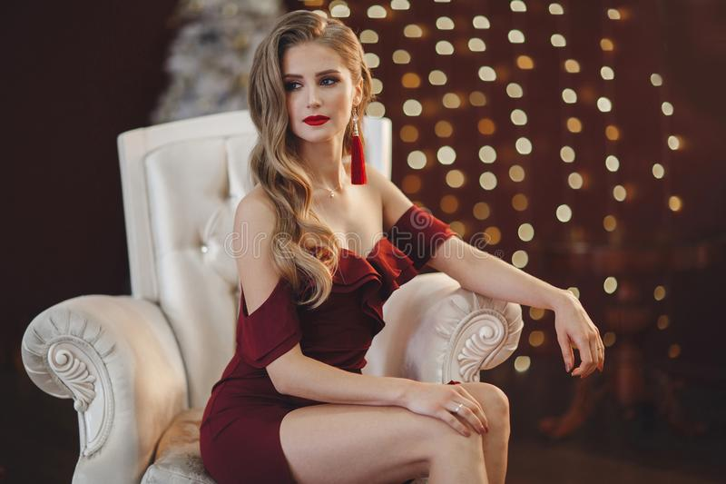 Beautiful woman in an elegant outdoor dress posing alone, sitting in a chair royalty free stock photography