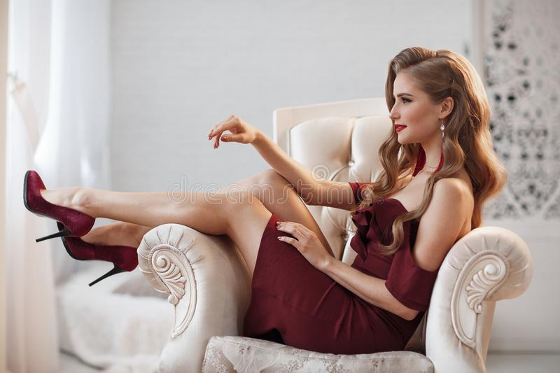 Beautiful woman in an elegant outdoor dress posing alone, sitting in a chair. Beautiful lady in an elegant burgundy dress. Close up fashion portrait of model royalty free stock image