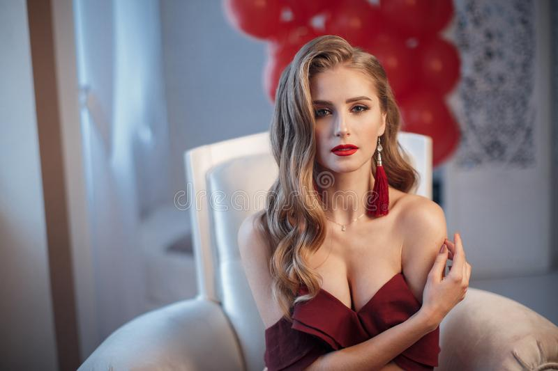 Beautiful woman in an elegant outdoor dress posing alone, sitting in a chair. Beautiful lady in an elegant burgundy dress. Close up fashion portrait of model stock photos