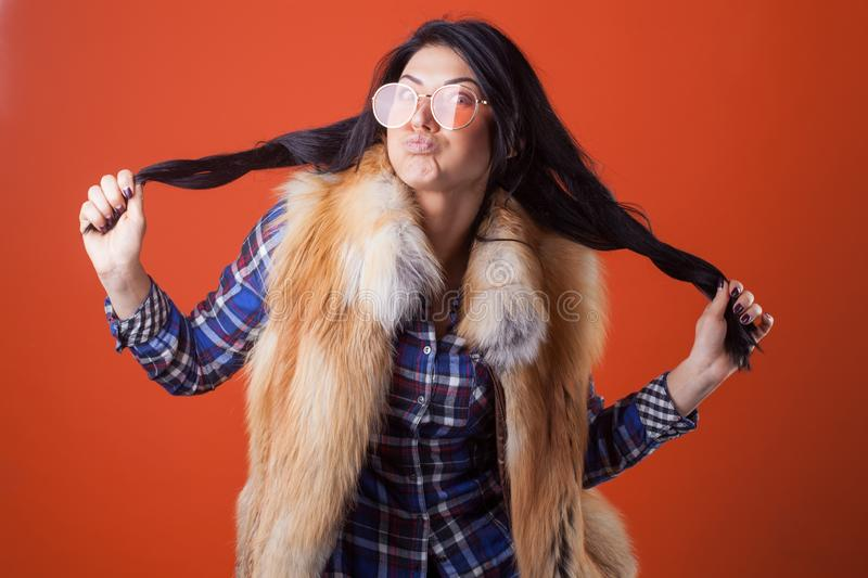 Pretty woman model pose wear plaid shirt and fur vest on the orange studio background royalty free stock image