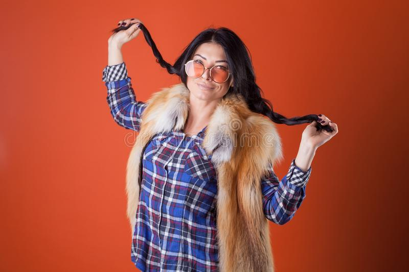 Pretty woman model pose wear plaid shirt and fur vest on the orange studio background royalty free stock photography