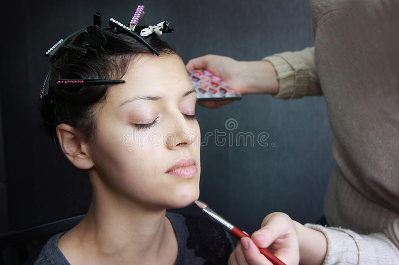 Beautiful model, applying make-up royalty free stock image