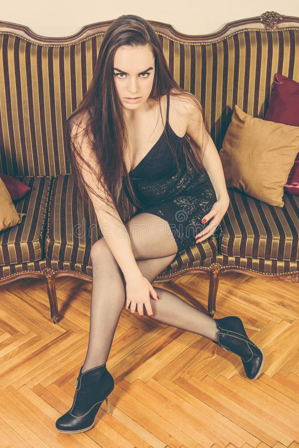 Beautiful person indoor looking seductive at camera. Sensual elegant woman posing on sofa. Image of beautiful luxurious female sitting on leather couch. Photo of stock photo