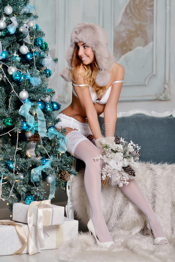 Beautiful Santa Clause in elegant panties, hat and bra. Fashion portrait of model girl indoors with christmas tree. Cute woman in lace white lingerie. Female stock photo