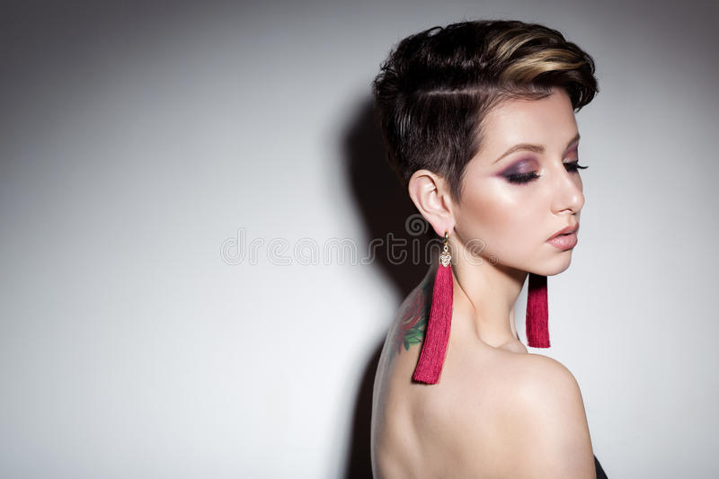 Beautiful sensual young girl with short hair with bright makeup in the nude, beautiful evening jewelry earrings, necklaces, b stock images