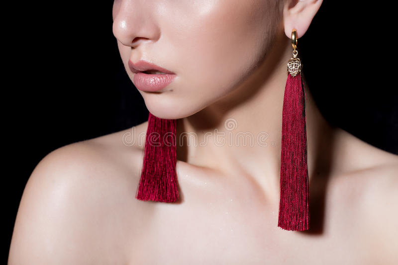 Beautiful sensual young girl with short hair with bright makeup in the nude, beautiful evening jewelry earrings, necklaces, b royalty free stock photos