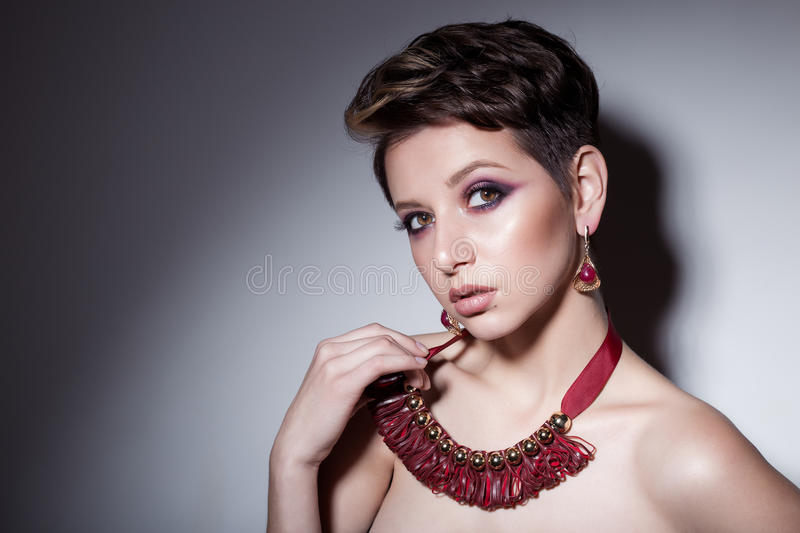 Beautiful sensual young girl with short hair with bright makeup in the nude, beautiful evening jewelry earrings, necklaces, b royalty free stock photography