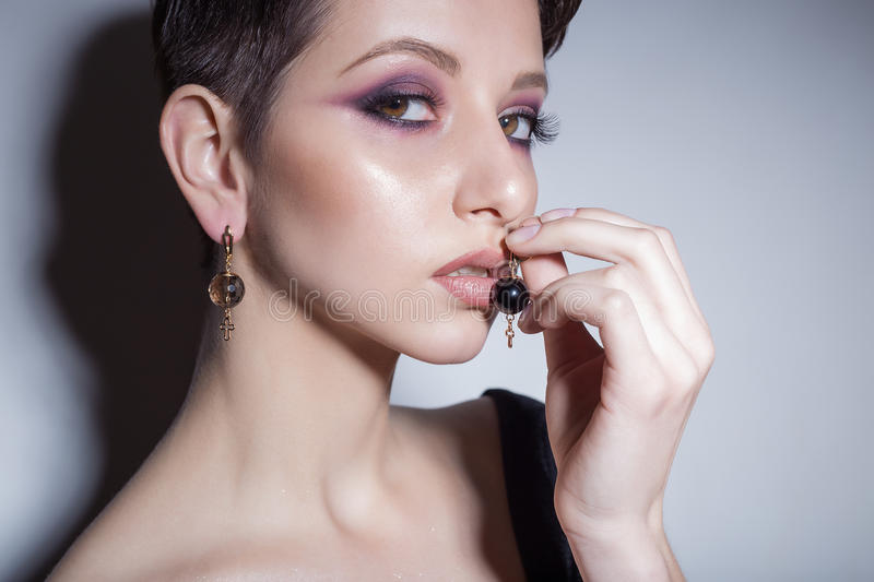 Beautiful sensual young girl with short hair with bright makeup in the nude, beautiful evening jewelry earrings, necklaces, b royalty free stock image
