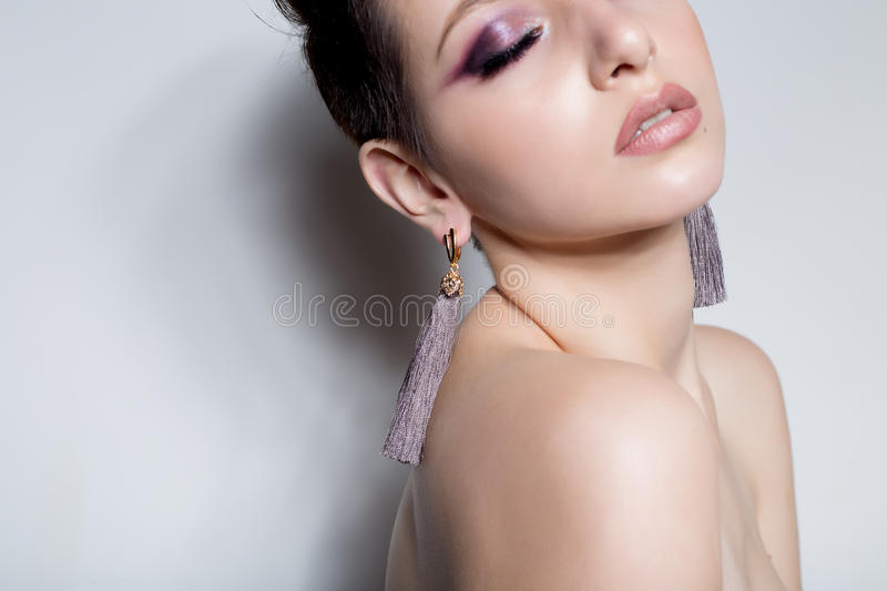 Beautiful sensual young girl with short hair with bright makeup in the nude, beautiful evening jewelry earrings, necklaces, b royalty free stock images