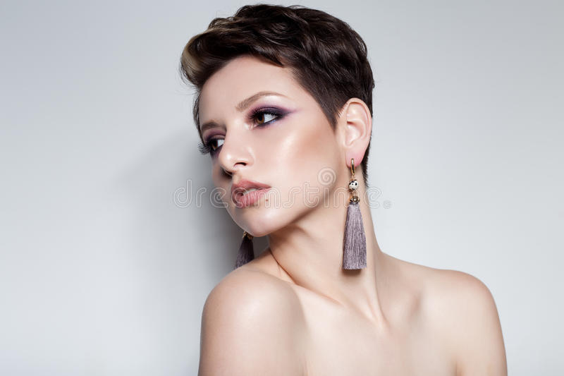 Beautiful sensual young girl with short hair with bright makeup in the nude, beautiful evening jewelry earrings, necklaces, b stock photo