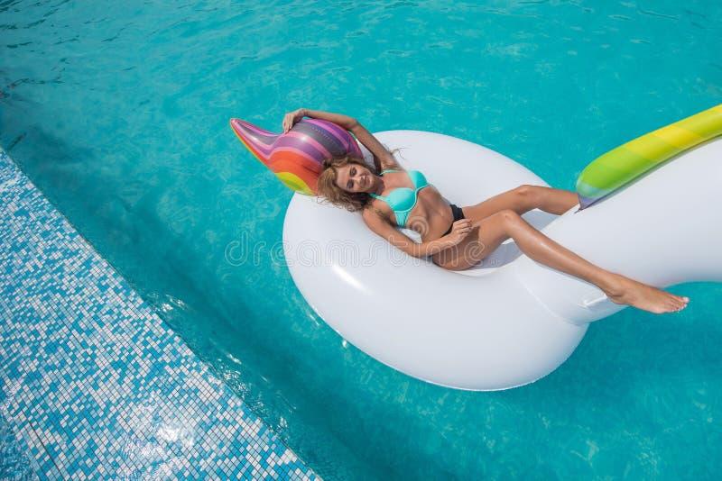 Beautiful slender blonde sitting big inflatable unicorn pool stock image